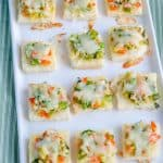 A platter of Bread Canapes on an olive green white stripes kitchen towel.