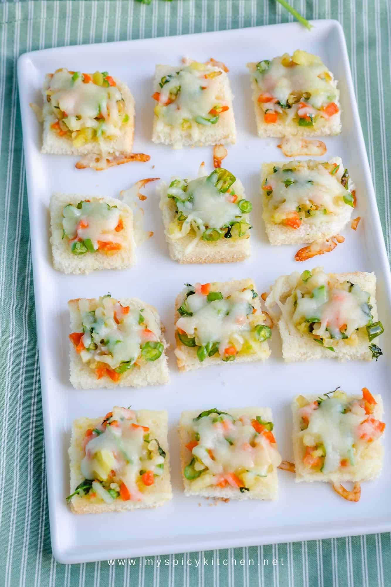 A platter of mixed vegetable Bread Canapes on an olive green white stripes kitchen towel.