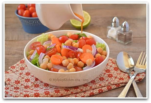 Pouring vinaigrette over a bowl of Chickpeas Salad.