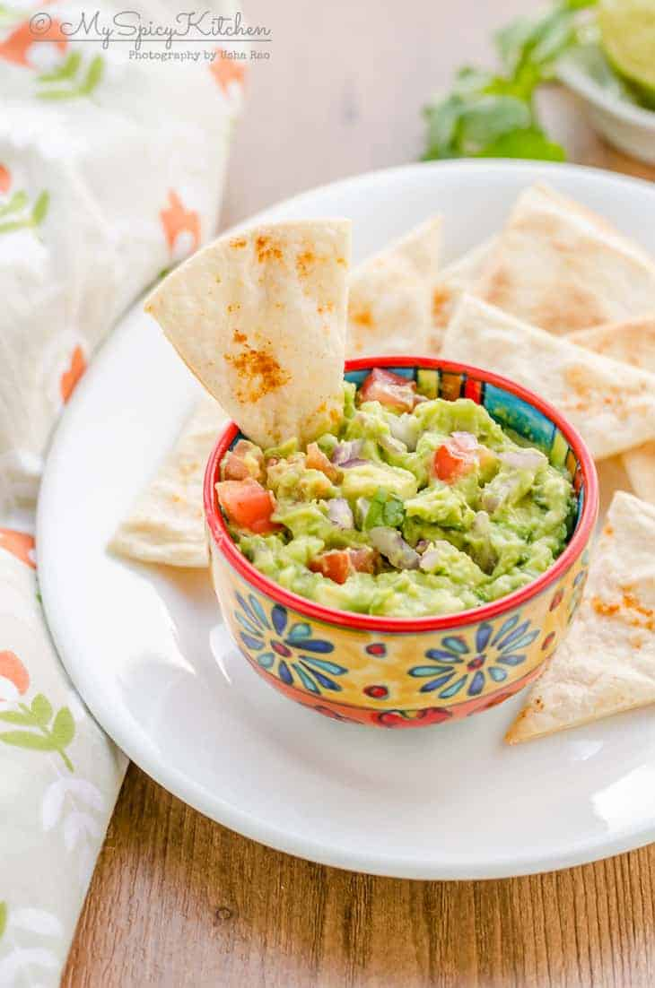 A bowl guacamole with baked baked tortilla chips