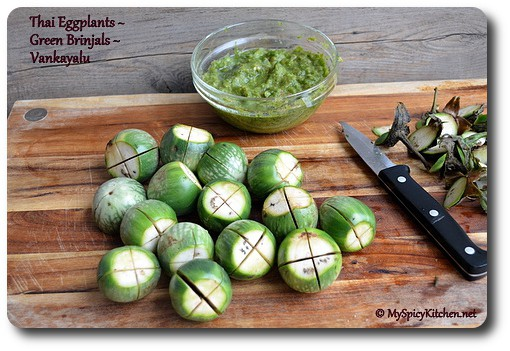 Thai eggplants and a bowl of cilantro green chili paste on a cutting board