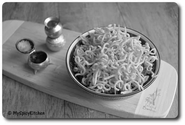 Black & white image a bowl of Alu Sev  on a long rectangle wooden board.
