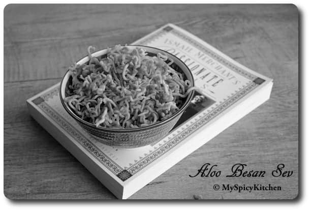 B&w image of bowl of aloo besan sev on a cookbook.