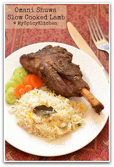 Omani Shuwa - slow cooked lamb on a plate with some salad and flavored rice