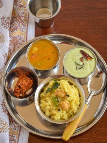 Platter of ven pongal, chutney, sambar and pickle.