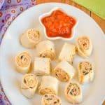 A platter of Fiesta pinwheels and a bowl of salsa