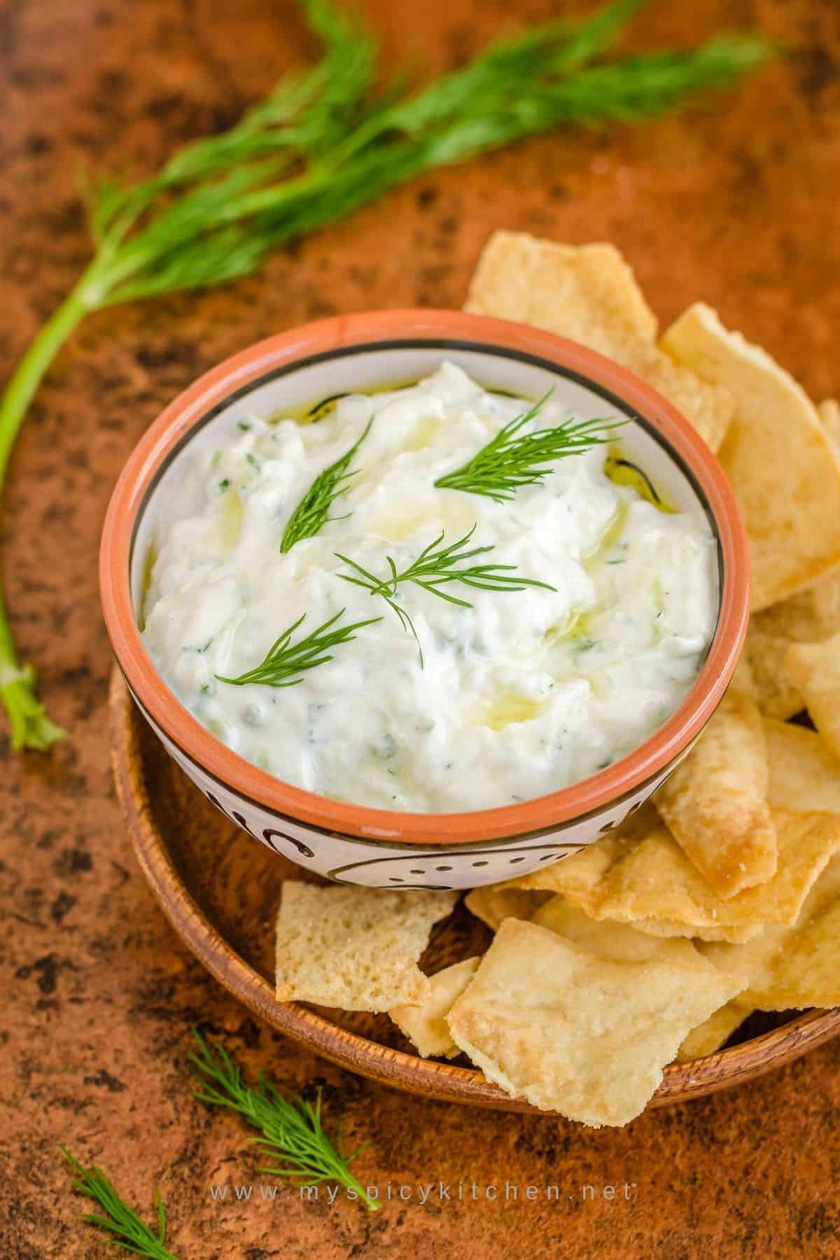 A bowl of tzatziki sauce with pita chips