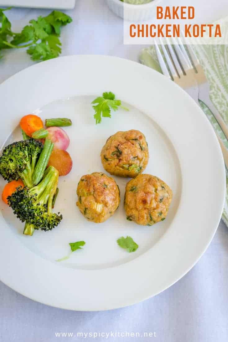 A plate of healthy baked chicken kofta (meatballs) seasoned with Indian spices and served with grilled vegetables.