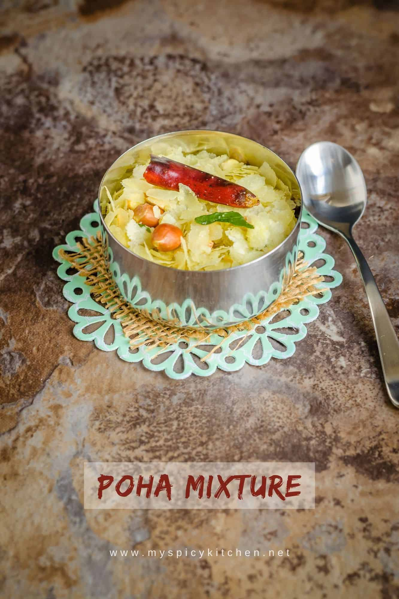 A bowl poha mixture is a savory Indian snack with flattened rice and peanuts.