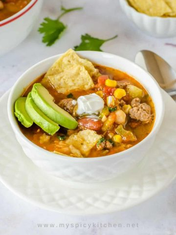 Lamb taco soup in a white bowl placed on a white plate.