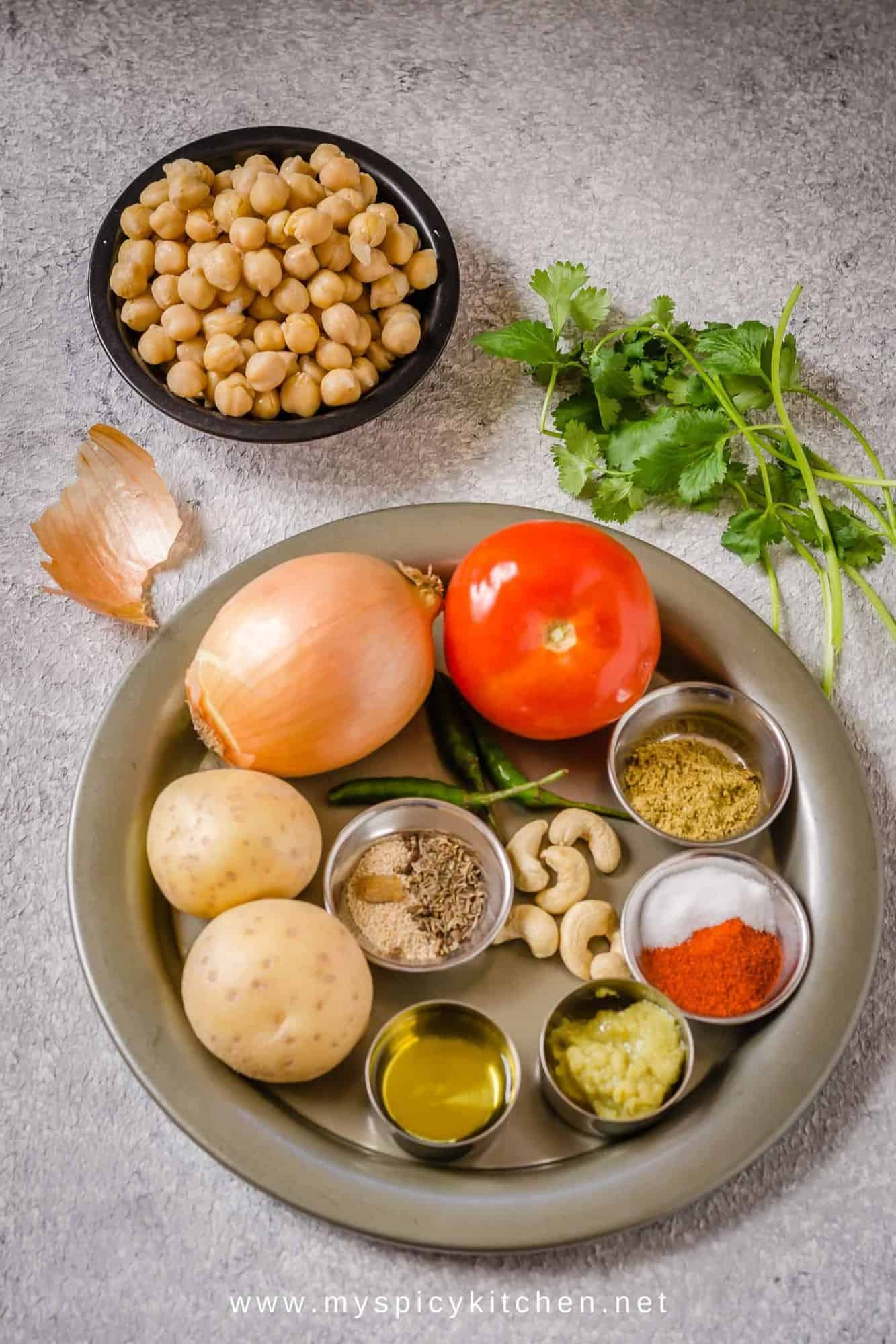 Ingredients for chana masala in a tray and chickpeas on the side.
