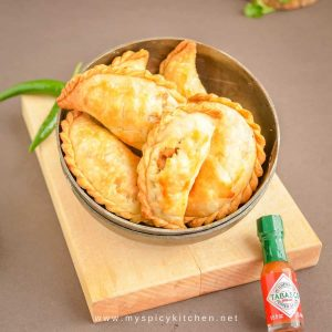Bowl of baked empanadas with mini bottle of tabasco sauce on the side