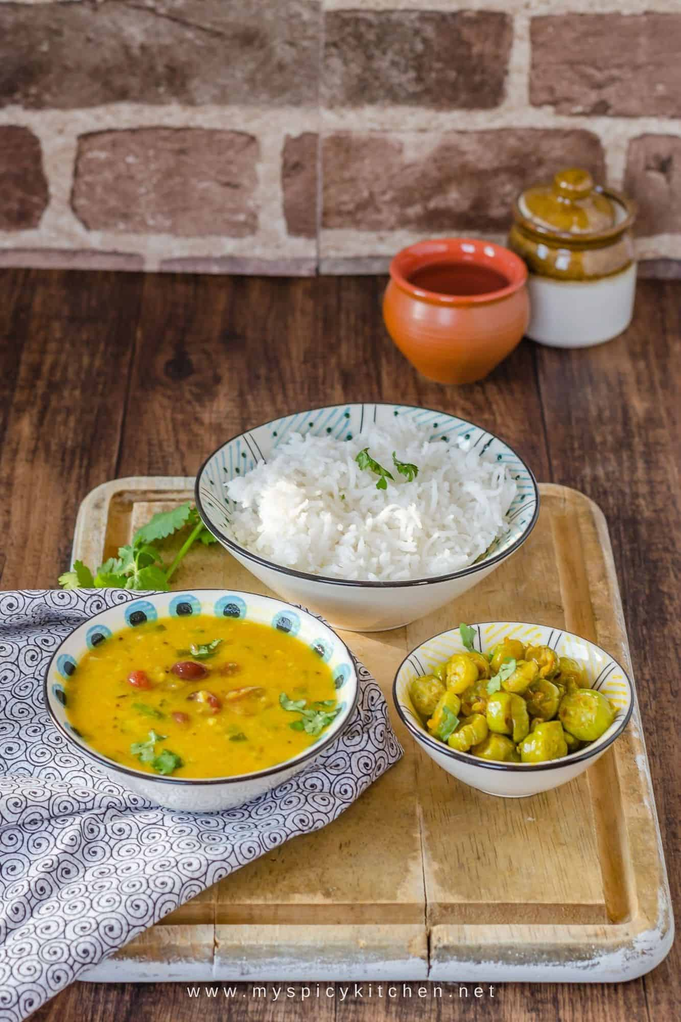 A simple meal, cranberry dal, ivy gourd fry and rice on a wooden board.