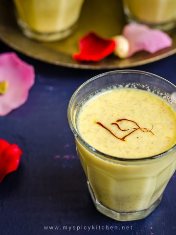 A glass of holi drink with saffron garnish.