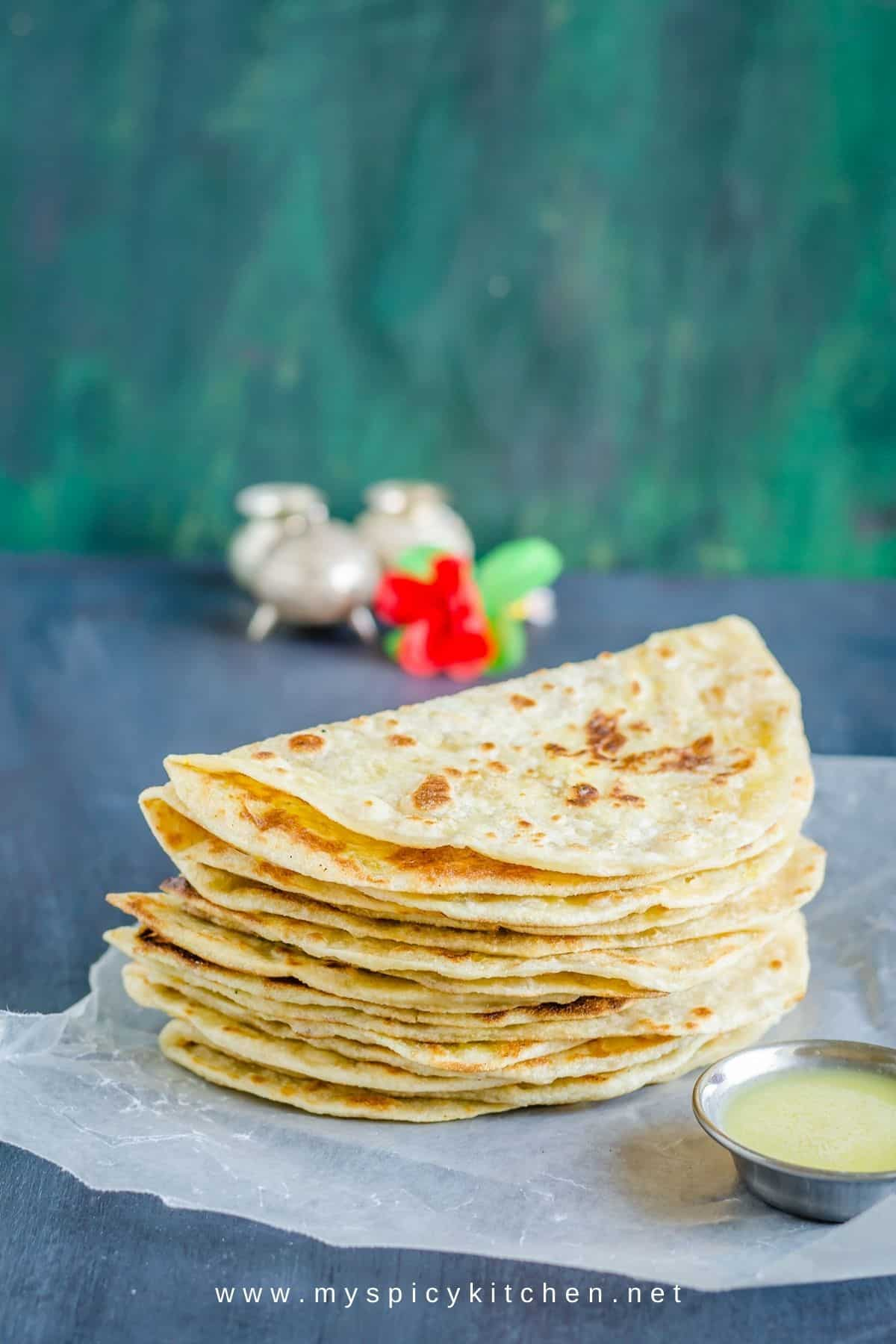 A stack of half folded moong dal pooran poli and a bowl of ghee on the side.