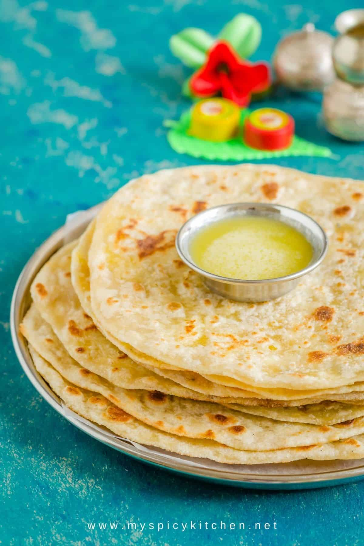 A stack of bakshalu with a bowl of ghee on top.