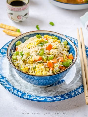 A bowl of Indo Chinese egg fried rice on a plate.