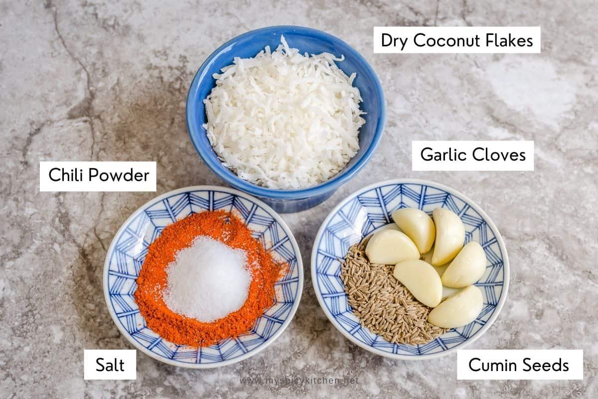 Ingredients for coconut garlic powder - coconut flakes, garlic cloves, cumin, salt and chili powder.