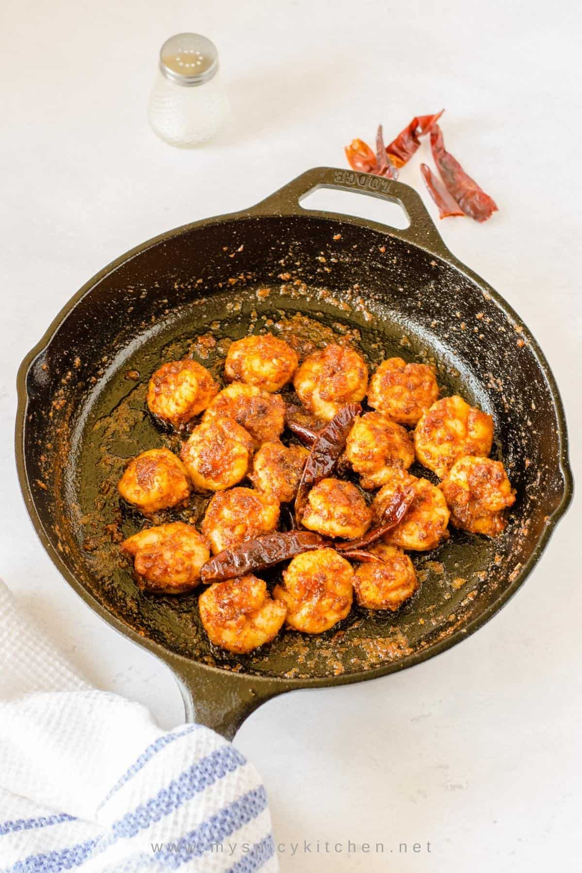 Chili garlic shrimp in a cast iron pan.
