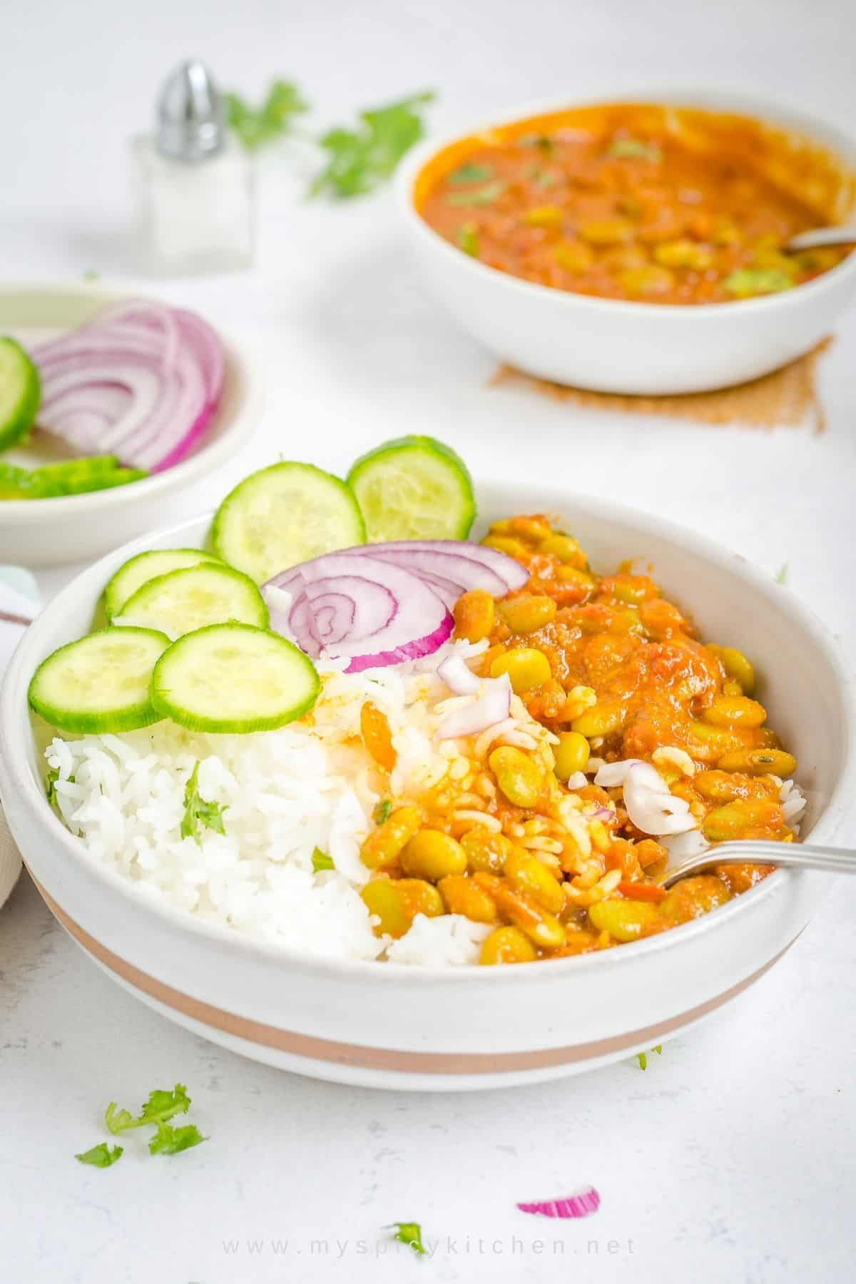 Bowl of rice, double beans curry, sliced cucumbers and onions.